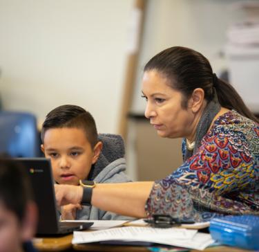Photo: teacher helping student on laptop